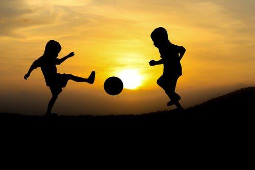 Kinder spielen im Sonnenuntergang Fußball