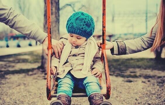 Ein kleines Mädchen sitzt auf einer Schaukel und die Eltern legen ihm jeweils eine Hand auf jede Schulter.