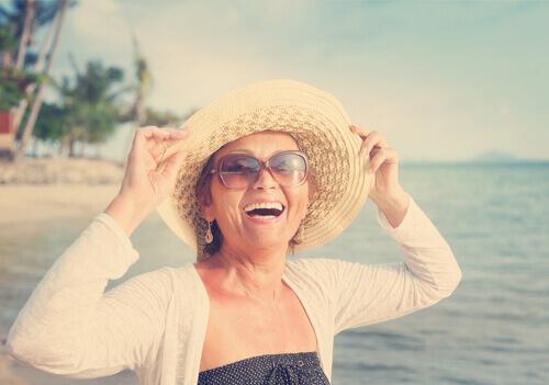 Lachende ältere Frau am Strand