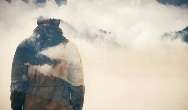 Ein Mann stehend von hinten, auf dessen Kleidung sich Mond und Wolken spiegeln.