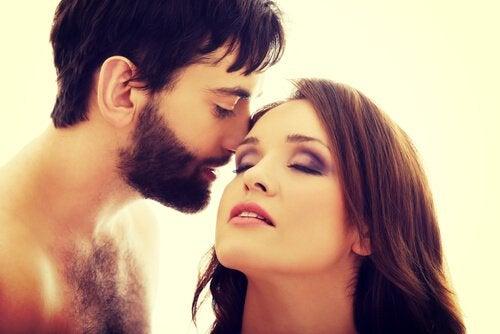 Mann flüstert seiner Partnerin etwas ins Ohr