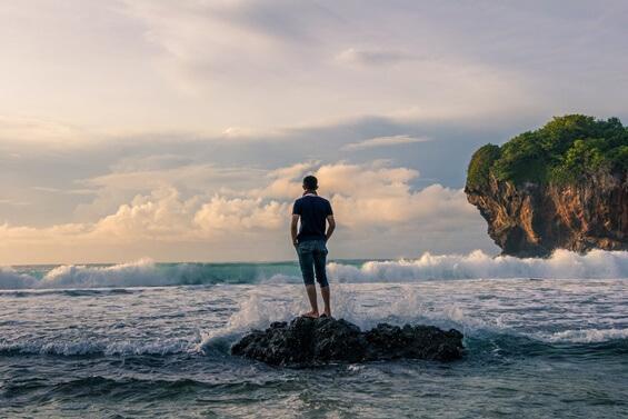 Mann steht auf einem Felsen im Meer