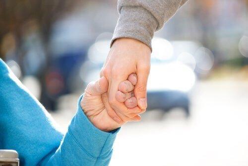 Eine Person hält die Hand einer älteren Person.