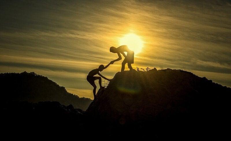 Person hilft einer anderen auf einen Berg