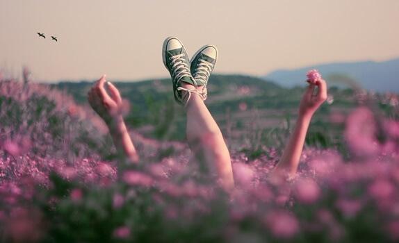 Frau streckt auf einer pinken Blumenwiese ihre Beine und Hände nach oben