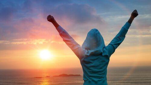 Eine Person reckt die Hände in Siegerpose zum Himmel, in dem die Sonne untergeht.