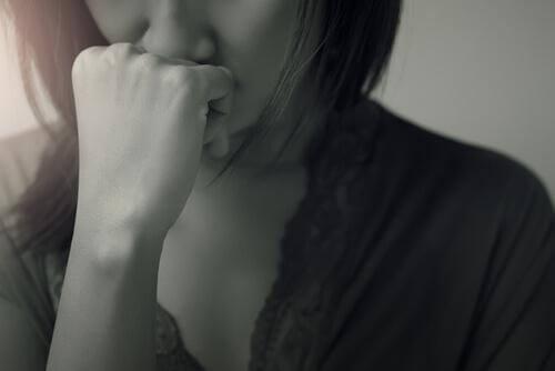 Schwarz-Weiß-Foto einer Frau, die sich die Faust vor den Mund hält und verzweifelt ist