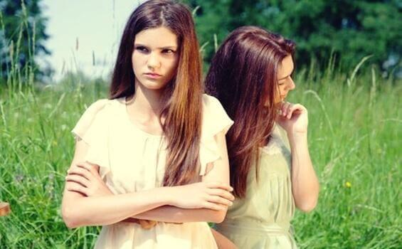 Junge Frau steht im Gras und schaut verärgert