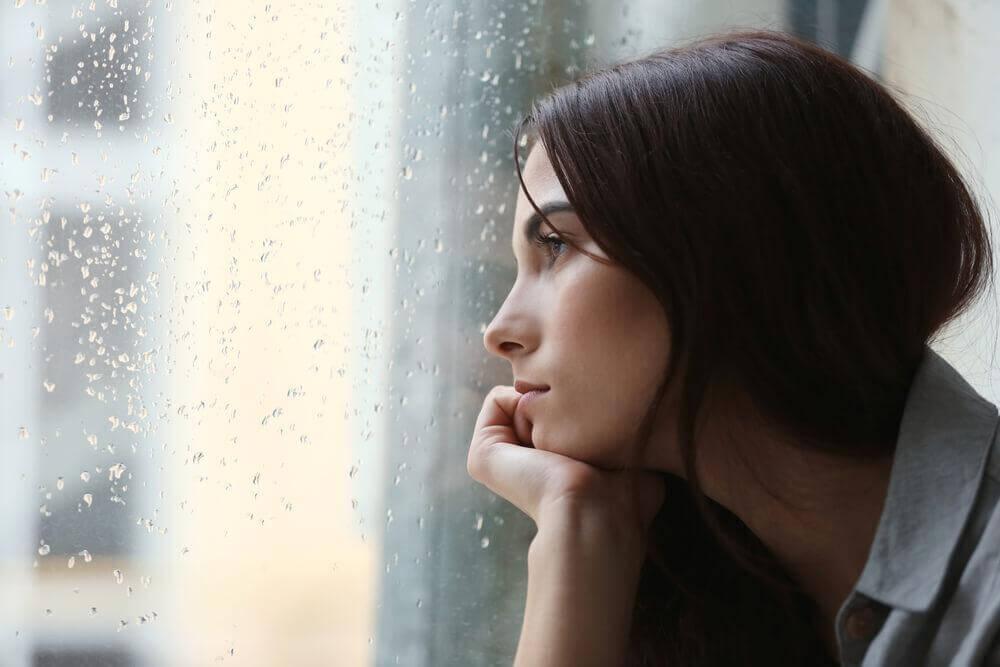 Depressive Frau schaut aus dem Fenster