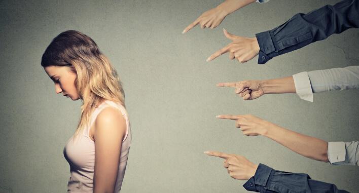 Fünf Menschen zeigen auf eine Frau mit geducktem Kopf