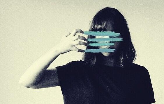 Zweck der Traurigkeit - Frau zerkratzt Bild vor ihrem Gesicht