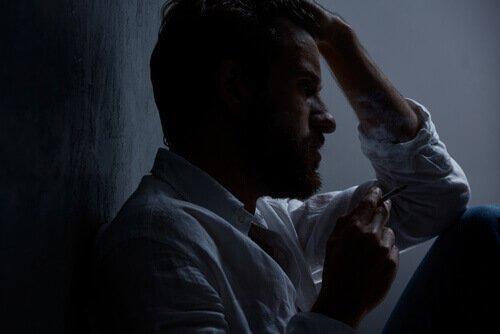 Ein Mann sitzt allein in einem dunklen Raum und raucht.