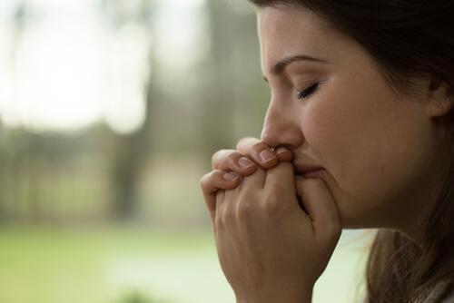 Eine traurige Frau hält ihre Hände vor den Mund, hat ihre Augen geschlossen.