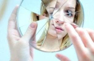Zu selbstkritisch - Eine junge Frau blickt in einen zerbrochenen Spiegel.