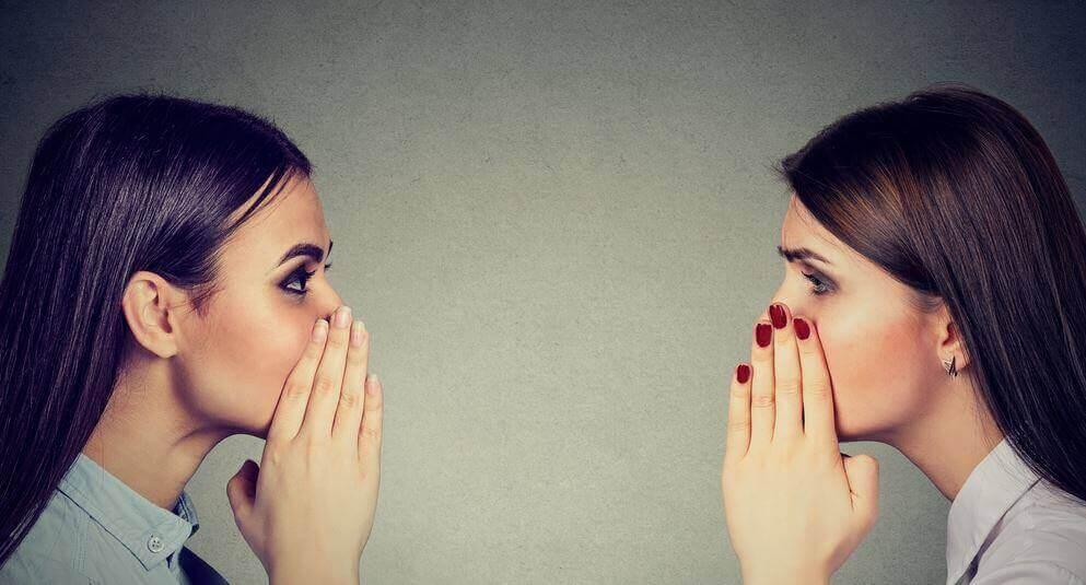 Zwei Frauen tuscheln hinter vorgehaltener Hand.