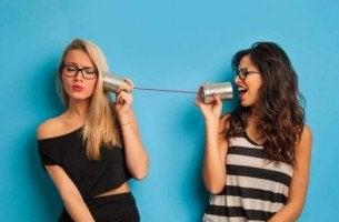 Klatsch und Tratsch - Zwei junge Frauen reden über ein Dosentelefon miteinander.