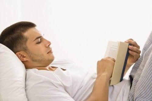 Mann, der im Bett liest
