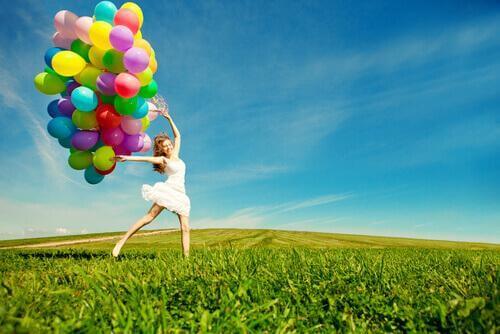 Frau, die viele Luftballons hält