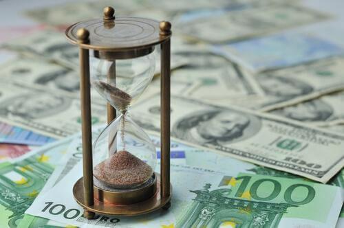 Ablaufende Sanduhr auf Geldscheinen