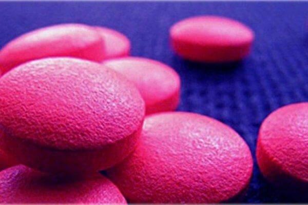 Rosafarbene Designerdrogen in Tablettenform auf blauem Untergrund.