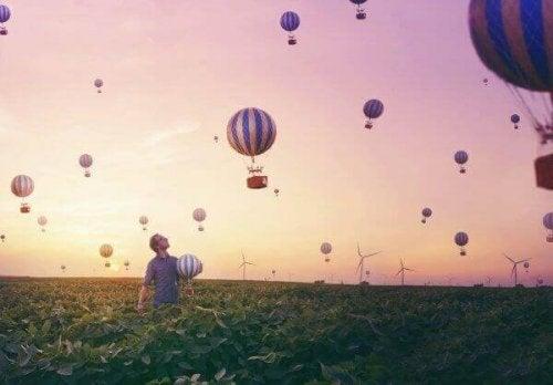 Mann in einem Feld unter zahlreichen Heißluftballons