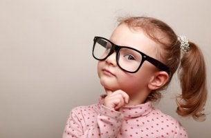 Moralische Entscheidungen - Kleines Mädchen hält sich fragend den Finger ans Kinn und denkt nach.