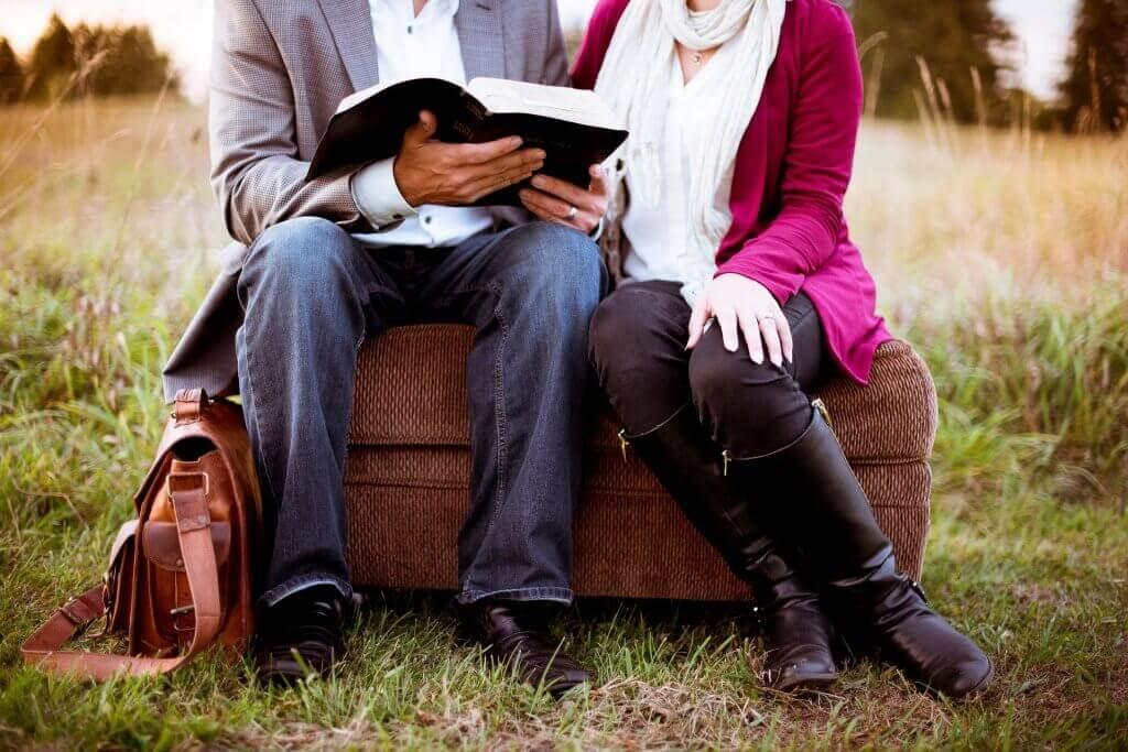 Paar sitzt auf einem Koffer und schaut in ein Buch