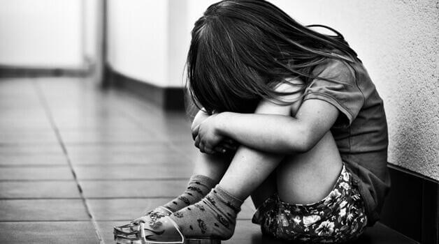 Schwarz-Weiß-Bild eines trauriges Mädchens am Boden