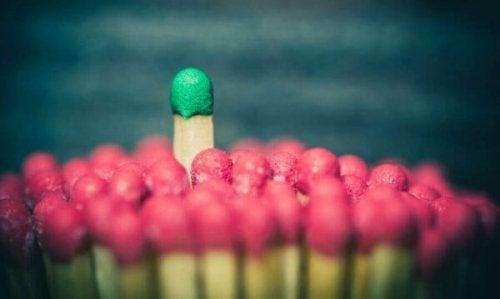 Streichholz mit grünem Kopf inmitten von Streichhölzer mit rotem Kopf