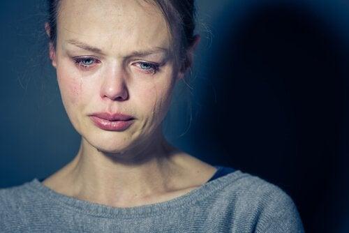 Eine blonde Frau weint.