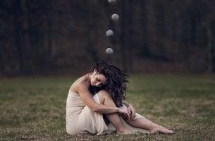 Auswirkung von Stress - Eine Frau sitzt müde auf einer Wiese.