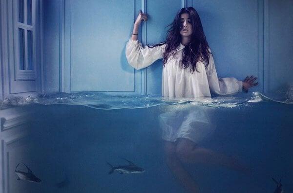 Eine Frau steht bis zum Bauch im Wasser.