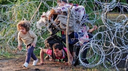 Flüchtlinge kriechen unter einem Zaun durch