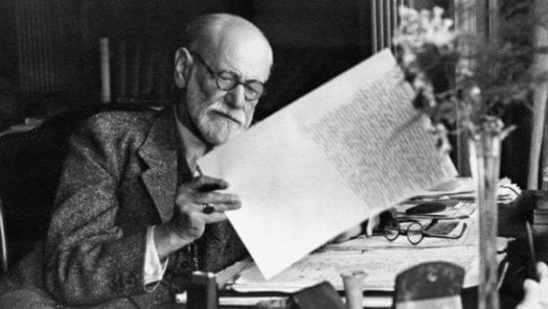 Freud sitzt an seinem Schreibtisch.