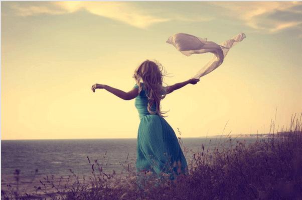 Frau tanzt mit einem Tuch in der Hand am Meer