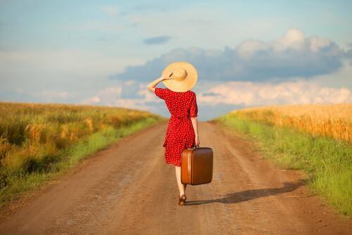 Frau mit Koffer auf einem Weg