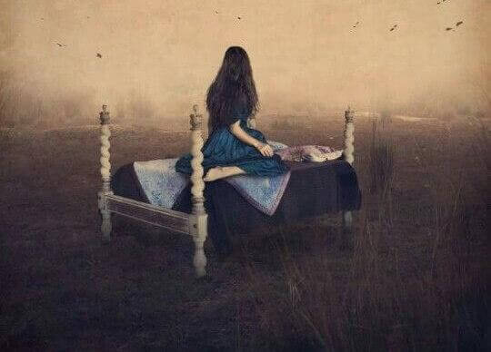 Frau sitzt auf Bett und schaut in die Ferne