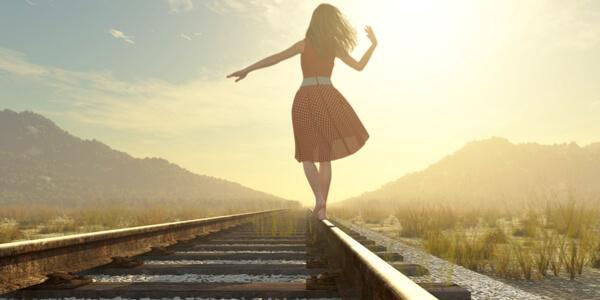 In einer abgeschiedenen Region läuft eine Frau auf Zuggleisen.