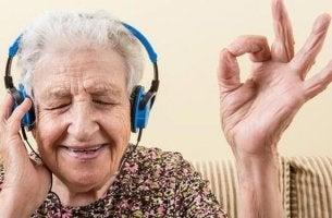 Musik und Alzheimer - Ältere Frau hört Musik über Kopfhörer.