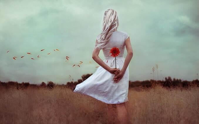 Blonde Frau hält hinter ihrem Rücken eine rote Blume