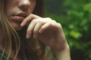 Sich selbst Probleme schaffen - nachdenkliche Frau mit Finger vor dem Mund