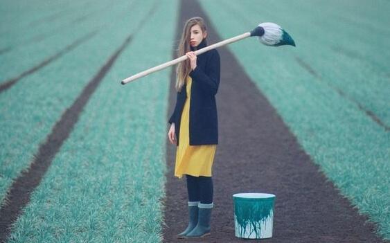 Frau steht mit einem großen Pinsel auf einem Rasen