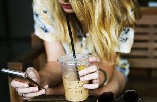 Neue Formen der Kommunikation - Frau mit Handy und Drink