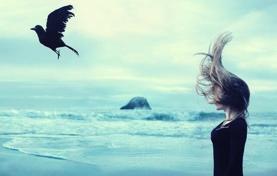 Frau steht am Meer und schaut auf einen fliegenden Raben
