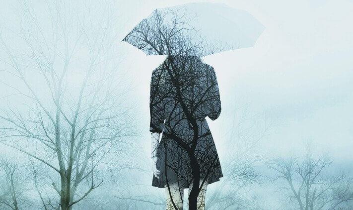 Frau mit Regenschirm in kaltem Winterwald