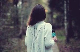 Frau mit Tasse in der Hand, die überlegt, ob sie gehen oder bleiben soll