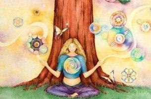 Emotionales Immunsystem - Frau sitzt unter einem Baum und jongliert Emotionen