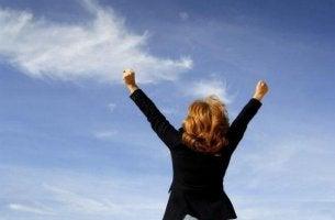 Umgang mit Misserfolgen - Eine Frau streckt die Arme in Siegerpose in Richtung Himmel.