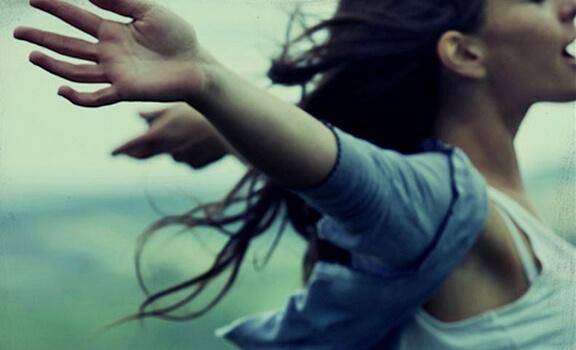 Erst etwas verlieren - Frau streckt die Arme aus und genießt den Moment