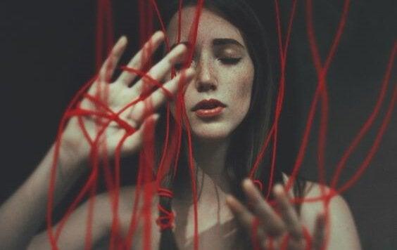 Frau umgeben von roten Schnüren